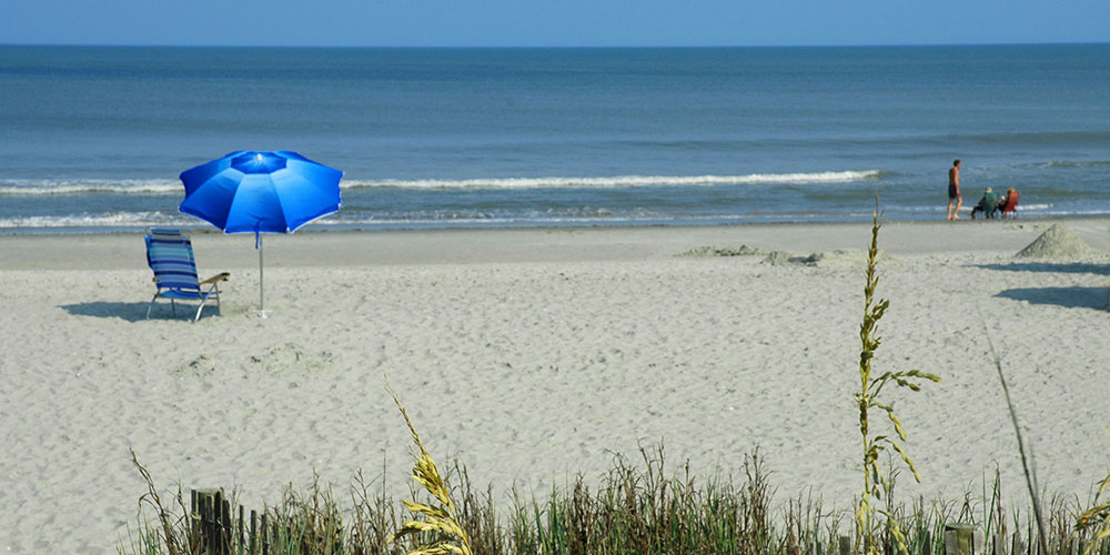 A blue umbrella and chair on the beach